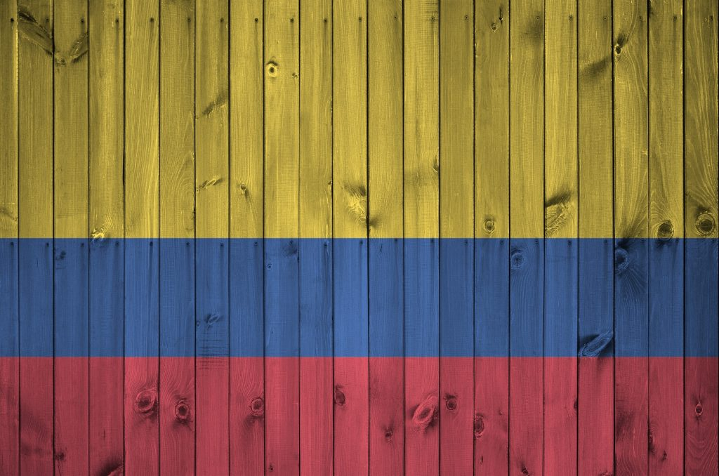 Colombia flag depicted in bright paint colors on old wooden wall close up