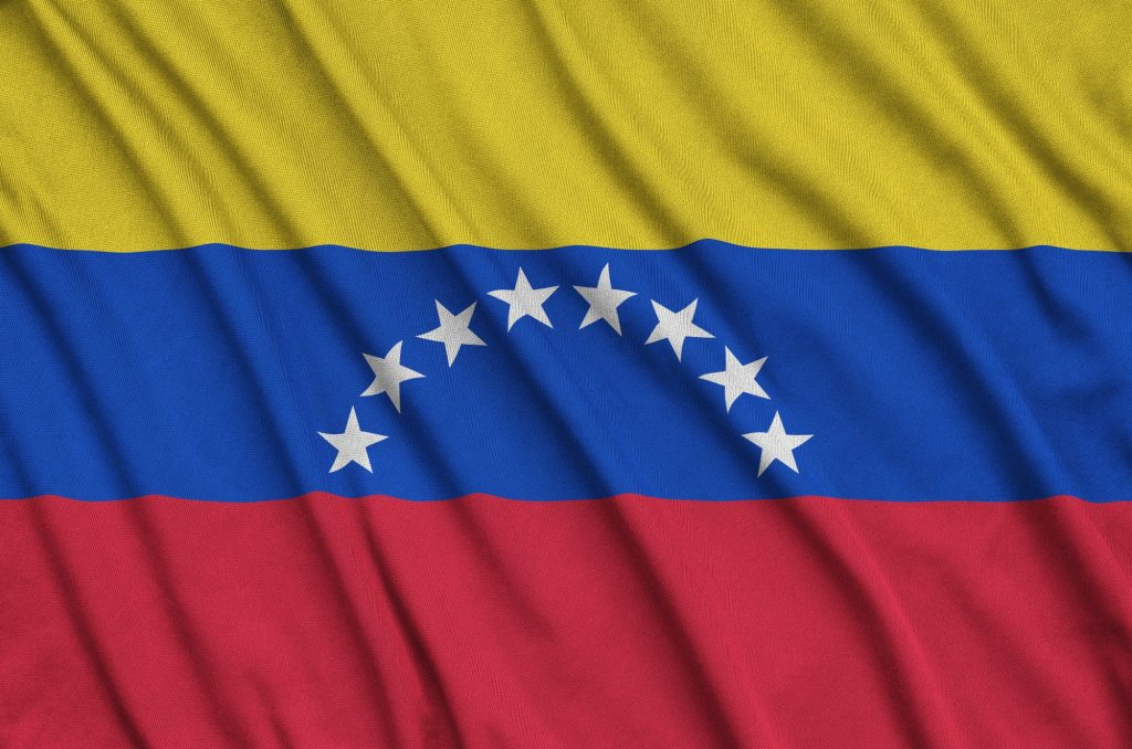 Venezuela flag is depicted on a sports cloth fabric with many folds. Sport team waving banner
